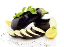 Sliced eggplants basil leaves,lemons,black pepper isolated white Stock Photos