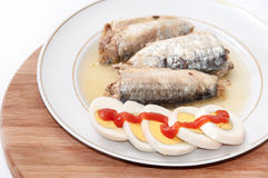 Sliced eggs with tomato ketchup and sardines served on the plate Stock Photos