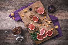Sliced figs on bread with jam and nuts in rustic style Stock Images