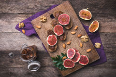 Sliced figs, nuts and bread with jam on choppingboard in rustic Royalty Free Stock Photography