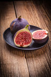 Sliced figs on a wooden table. Stock Photos