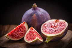 Sliced figs on a wooden table. Royalty Free Stock Image