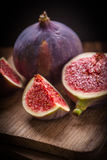 Sliced figs on a wooden table. Top view. Royalty Free Stock Image