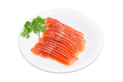 Sliced fillet of salted rainbow trout on a white dish. Sliced fillet of salted rainbow trout and a sprig of parsley on a white dish on a light background Stock Photography