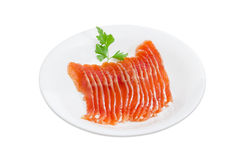 Sliced fillet of salted rainbow trout on a white dish. Sliced fillet of salted rainbow trout and a sprig of parsley on a white dish on a light background Stock Image