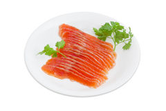 Sliced fillet of salted rainbow trout on a white dish. Sliced fillet of salted rainbow trout and a sprigs of parsley on a white dish on a light background Royalty Free Stock Images