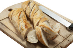 Sliced french baguette bread. Slices of fresh french bread on wooden cutting board with a bread knife Royalty Free Stock Photography