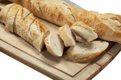 Sliced french baguette bread. Slices of fresh french bread on wooden cutting board with a bread knife Royalty Free Stock Photo