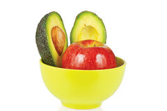 Sliced fresh avocado and apple in ceramic cup Royalty Free Stock Photos