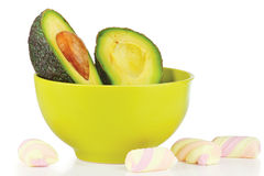 Sliced fresh avocado in ceramic cup and candies Royalty Free Stock Photography