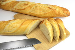 Sliced fresh baguette and bread knife. On white background Royalty Free Stock Photography