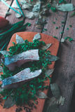 Sliced fresh fish with spices and parsley on a wooden board. Stock Image