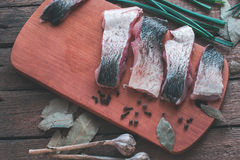 Sliced fresh fish with spices and parsley on a wooden board. Royalty Free Stock Photos