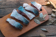 Sliced fresh fish with spices and parsley on a wooden board. Royalty Free Stock Images