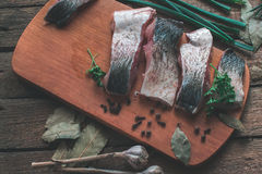 Sliced fresh fish with spices and parsley on a wooden board. Stock Images