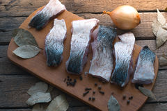 Sliced fresh fish with spices and parsley on a wooden board. Stock Photography
