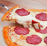 Sliced fresh flavorful pepperoni pizza on wood Stock Images