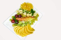 Sliced fresh fruit in a white plate. On a white background.Copy space Royalty Free Stock Photography