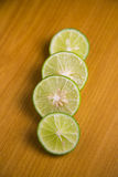 Sliced fresh green lemon on a brown wooden background Stock Photography