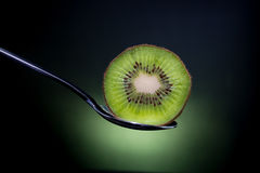Sliced fresh and juicy green kiwi fruit on spoon with green ligh Stock Photo