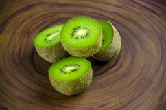 Sliced fresh and juicy kiwi fruit halves on a wooden background.  royalty free stock photos