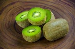 Sliced fresh and juicy kiwi fruit halves on a wooden background.  stock photos