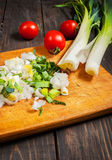 Sliced fresh leek on wooden board with tomatoes Stock Photography
