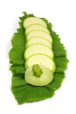 Sliced fresh light green zucchini on horseradish leaf isolated on white Royalty Free Stock Image