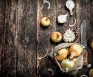 Sliced fresh onion with old hatchet. On a wooden background Royalty Free Stock Image