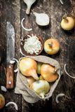 Sliced fresh onion with old hatchet. On a wooden background Stock Image