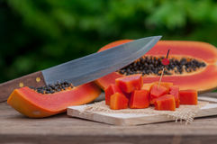 Sliced fresh Papaya fruit on wooden table with nature background.  Royalty Free Stock Photography