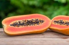 Sliced fresh Papaya fruit on wooden table with nature background.  Royalty Free Stock Photo