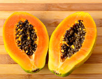 Sliced fresh papaya on wooden background Stock Photography