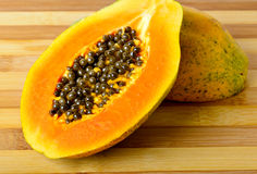 Sliced fresh papaya on wooden background Stock Image