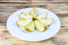 Sliced fresh pears in white plate on rustic wooden table Royalty Free Stock Photos