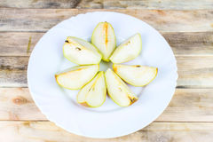 Sliced fresh pears in white plate on rustic wooden table Stock Photos