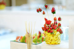 Sliced fresh pineapple and strawberries on sticks Royalty Free Stock Images
