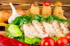 Sliced fresh pork lard, fresh produce, greens, vegetables on the wooden board, close-up, selective focus. Stock Photos