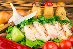 Sliced fresh pork lard, fresh produce, greens, vegetables on the wooden board and knife on table, selective focus. Stock Image
