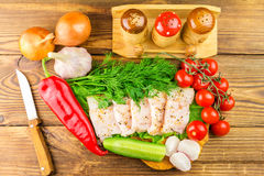 Sliced fresh pork lard, fresh produce, greens, vegetables on the wooden board and knife on table, top view. Royalty Free Stock Photo