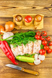 Sliced fresh pork lard, fresh produce, greens, vegetables on the wooden board and knife on table, top view. Stock Photos