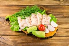 Sliced fresh pork lard, fresh produce, vegetables on the wooden board. Stock Photos