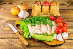 Sliced fresh pork lard, fresh produce, vegetables on the wooden board and knife on table. Royalty Free Stock Photography