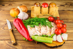 Sliced fresh pork lard, fresh produce, vegetables on the wooden board and knife on table. Stock Images