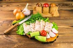 Sliced fresh pork lard, fresh produce, vegetables on the wooden board and knife on table. Stock Photos