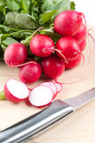 Sliced fresh radishes. Sliced and whole fresh radishes on a chopping board with a sharp stainless steel knife Royalty Free Stock Photo
