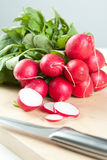 Sliced fresh radishes with a knife. Sliced and whole fresh radishes on a chopping board with a sharp stainless steel knife preparing ingredients for salad Stock Photography