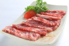 Sliced fresh raw beef on white plate with tomato and herbs. Deliciously Stock Image
