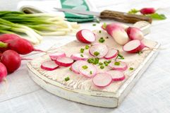Sliced fresh red radishes and green young onions on white wooden background. Healthy diet with radish. Ingredients for a light spring vegetable salad. Close Stock Photo