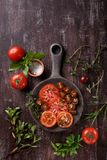 Sliced fresh red tomatoes with spices and herbs stock photography